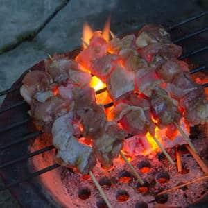 Hähnchenspieße auf dem Grillrost eines thailändischen Grills und glühende Kohlen.
