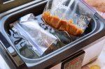 Vakuumbeutel oder Gefrierbeutel werden in das Wasserbad des Sous-Vide Gerätes gelegt.